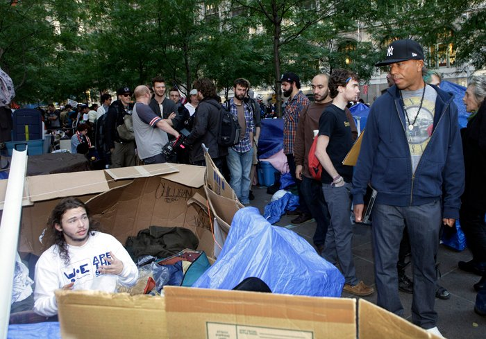 Hip hop mogul Russell Simmons, right, listens to a protester at the camp for the Occupy Wall Street demonstration in New York on Sunday.