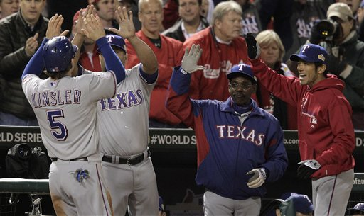 Texas Rangers' Ian Kinsler is congratulated in the dugout after scoring on a sacrifice fly ball during the ninth inning of Game 2 of baseball's World Series against the St. Louis Cardinals on Thursday in St. Louis.