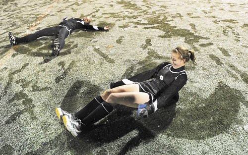 TIME FOR FUN: Skowhegan's Mikayla Toth, left, and Allison Lancaster, right, celebrate their victory over Marshwood in the Class A field hockey state championship game Saturday at Yarmouth by making snow angels. It was the Indians' 10th title in the last 11 seasons.