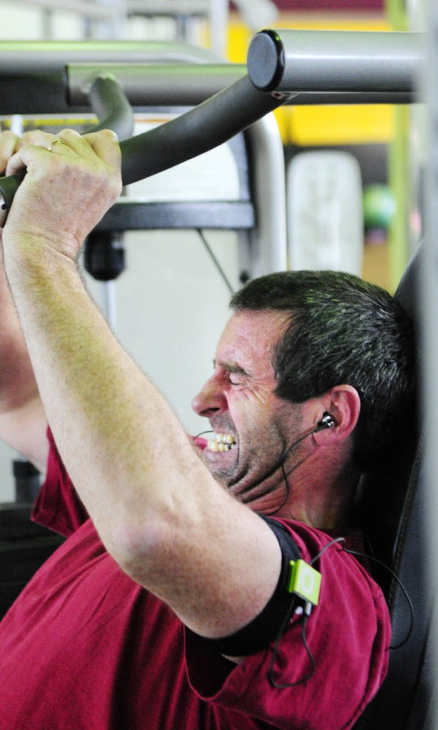 APPLE'S REACH: Vinnie McGuire lifts weights while he listens to music from the Apple iPod shuffle strapped on his arm on Thursday at the Planet Fitness in Augusta.
