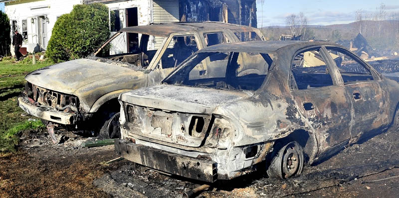 Two cars parked near the home and barn owned by Doug and Mary Lou Harlow were destroyed by a fast moving fire at the residence on the Dore Hill Road in Athens Tuesday evening.