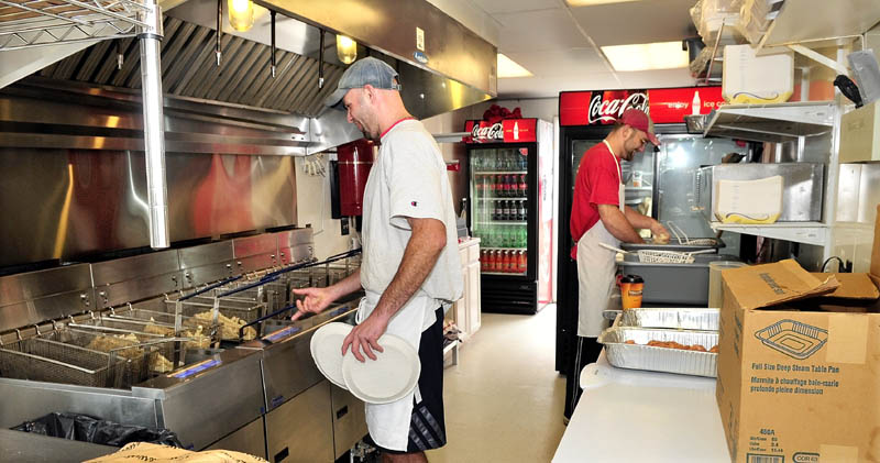 EXPANDING THE BUSINESS: Manager Shane Benedict, left, and employee Jeremy Bailey prepare food orders Wednesday at The Red Barn, a drive-through restaurant that opened recently on Bay Street in Winslow. The drive-through occupies a 10-foot-by-30-foot building that's seen multiple food tenants in recent years.