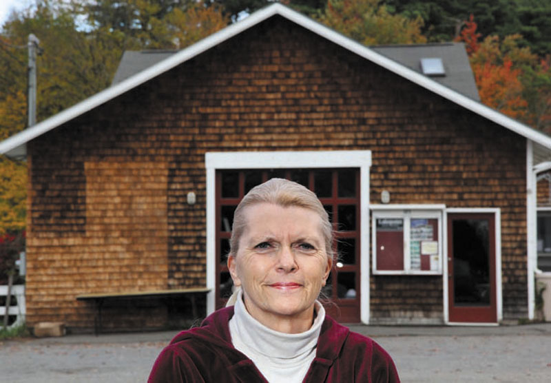 Jan Partridge, owner of Balloons & Things in Belgrade Lakes, has collected a petition with signatures from more than 100 people wanting to save the old marina (background) across from her store on Main Street.