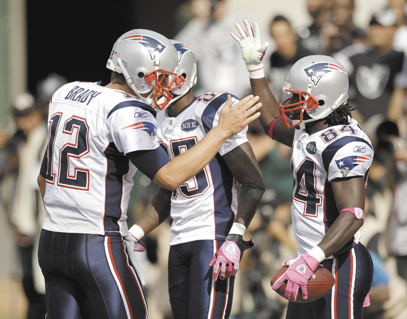 WAY TO GO: New England quarterback Tom Brady, left, greets wide receiver Deion Branch (84) after Branch caught a 4-yard pass for a touchdown in the fourth quarter of the Patriots' 31-19 win over the Oakland Raiders on Sunday in Oakland, Calif. NFLACTION11;