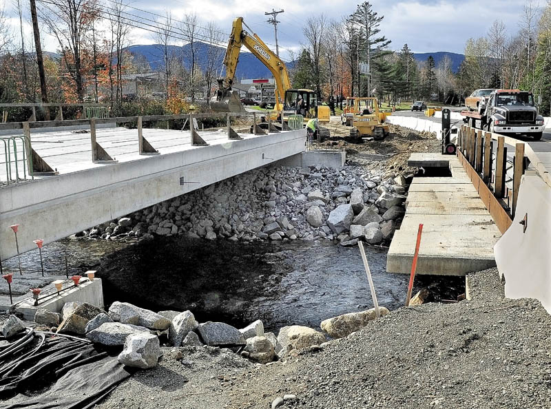 BYPASS: A truck passes over a temporary bridge Monday as workers with Jordan Excavation build up the roadway to the new replacement bridge over Brackett Brook in Carrabassett Valley. The bridge washed out during Tropical Storm Irene in August.