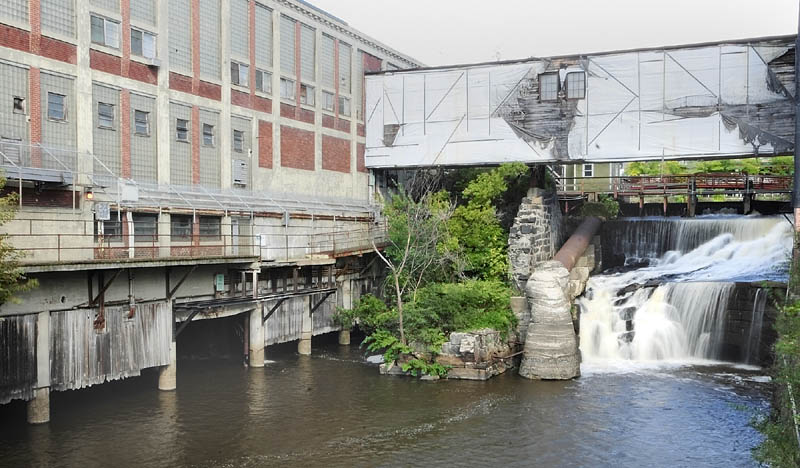A waterfall that used to be used for hydropower runs past the Bates Mill No. 5 in Lewiston, the proposed site of a casino.