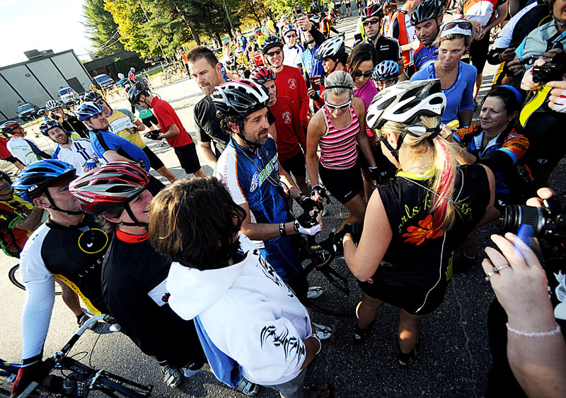SWARMED: Actor Patrick Dempsey, center, is swarmed by fans Sunday at the first rest stop in the parking lot of Thos. Moser in Auburn on the cycling route of the Dempsey Challenge. Dempsey signed jerseys, bib numbers and also took countless photos with people along the 50 miles he biked.