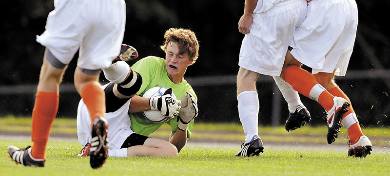 HOLDING ON: Erskine Academy goalkeeper Ryan Pulver collects a shot on net during a game against Brunswick High School in South China.