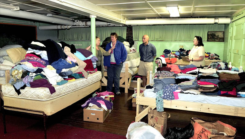 SHELTER FROM THE STORM: Members of the Waterville Area Homeless Action Group tour a dormitory filled with donated beds and clothing collected to meet the needs of homeless at the First Baptist Church in Waterville. From left are Amy Przytulski, Jen Reed, Michael Roy and the Rev. Arlene Tully.