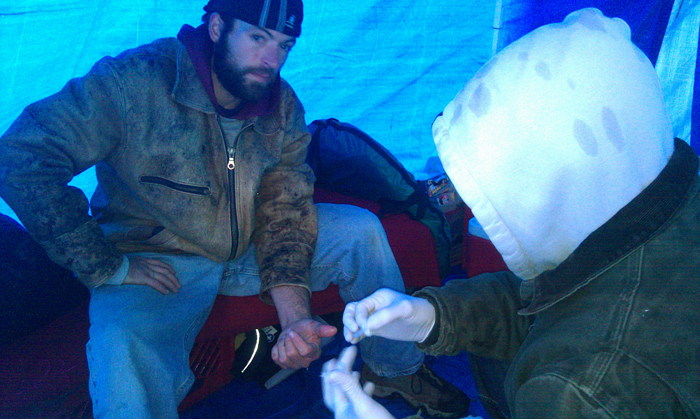Christopher Makelys, who is in charge of medical care at the Occupy Maine encampment in Portland's Lincoln Park, treats a cut on the finger of fellow protester Larry Vanscyoc in the group's medical tent.