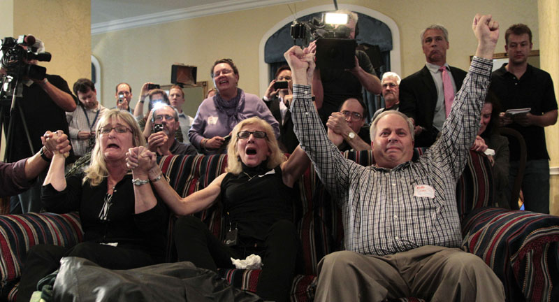 JUBILATION: Supporters of Amanda Knox react as they watch a television news broadcast about her successful appeal verdict Monday in a hotel suite in Seattle.