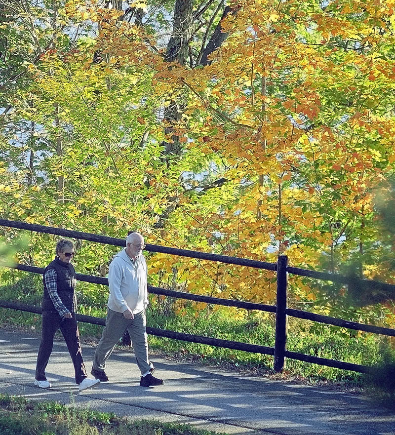 People walk along the Kennebec River Rail Trail on a sunny Saturday morning in Augusta.