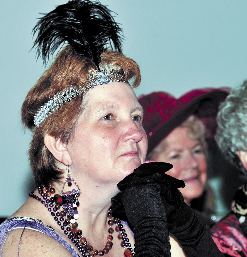 A SPOT OF TEA: Diane Louten, left, dressed as a flapper and Shirley Chaffee wore a signature hat as the Red Hat Society and others listen to quilter Debbie Quirion during the REM Vintage Tea social Sunday at the Center in Waterville. Dozens dined on gourmet hors d'oeuvres and desserts.