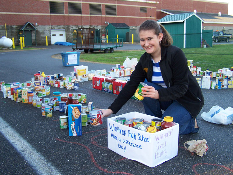 Maureen Tierney lines up cans and other items donated to the Make a Difference Day collection at Winthrop middle and high schools on Friday. The food was delivered to the Winthrop Food Pantry.