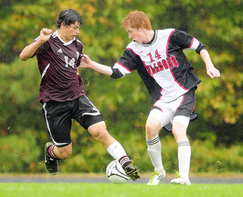 Monmouth Academy's Russell Neal, left, and Hall-Dale's Colin Lush battle for the ball during a game on a rainy Thursday afternoon at Hall-Dale High in Farmingdale.
