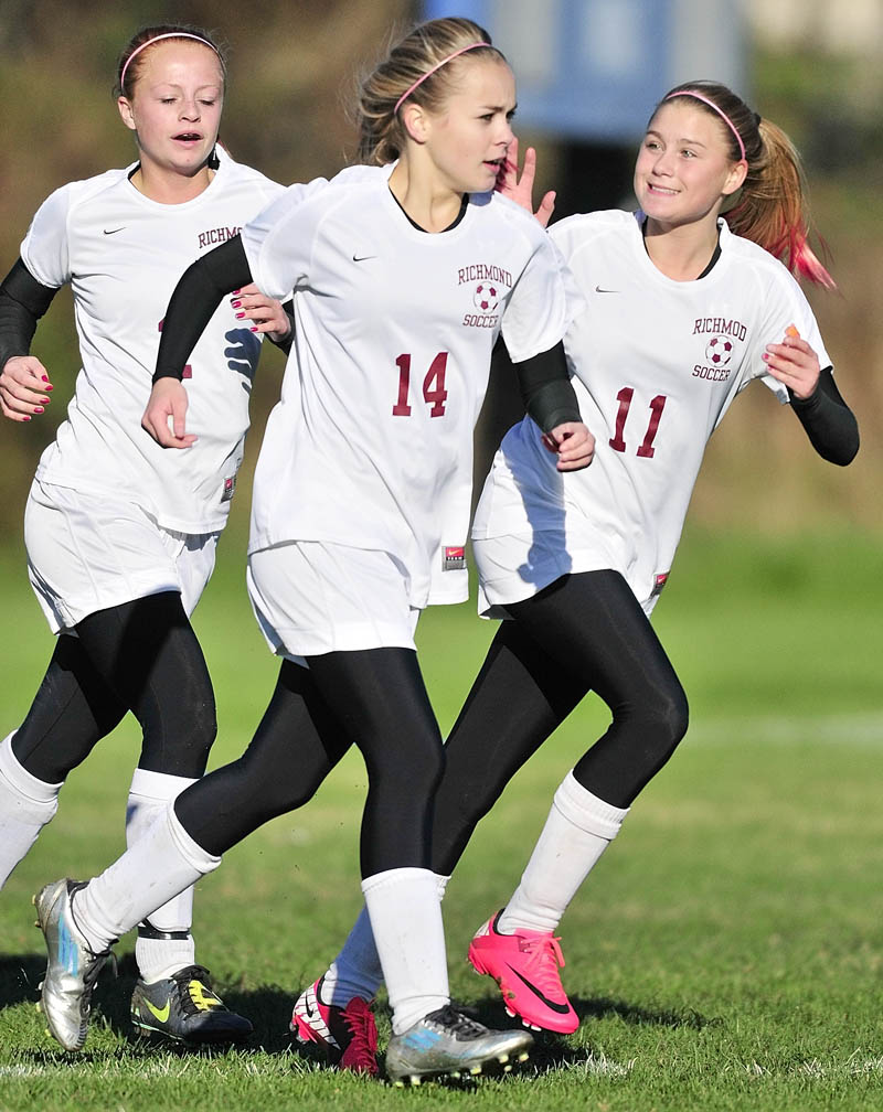 Noell Acord, left, Amber Loon and Micheala Lewis celebrate after a Richmond goal by their teammate Saige Strout during a game on Friday afternoon in Richmond.