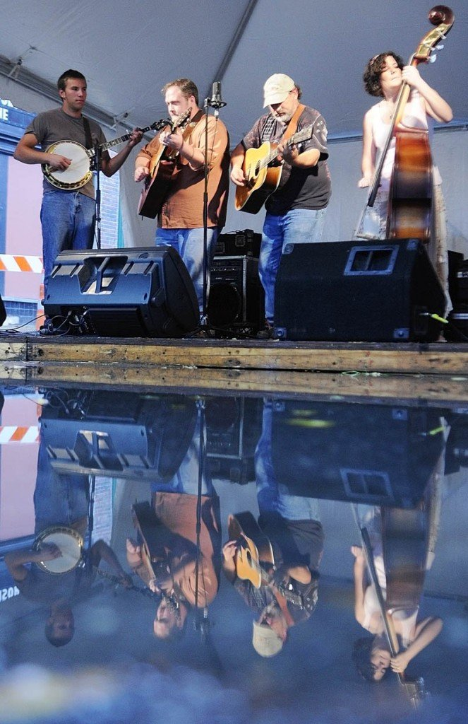 The Phat Grass band is reflected in a puddle in the middle of Water Street as they perform during Swine & Stein festivities Saturday on Water Street in downtown Gardiner.