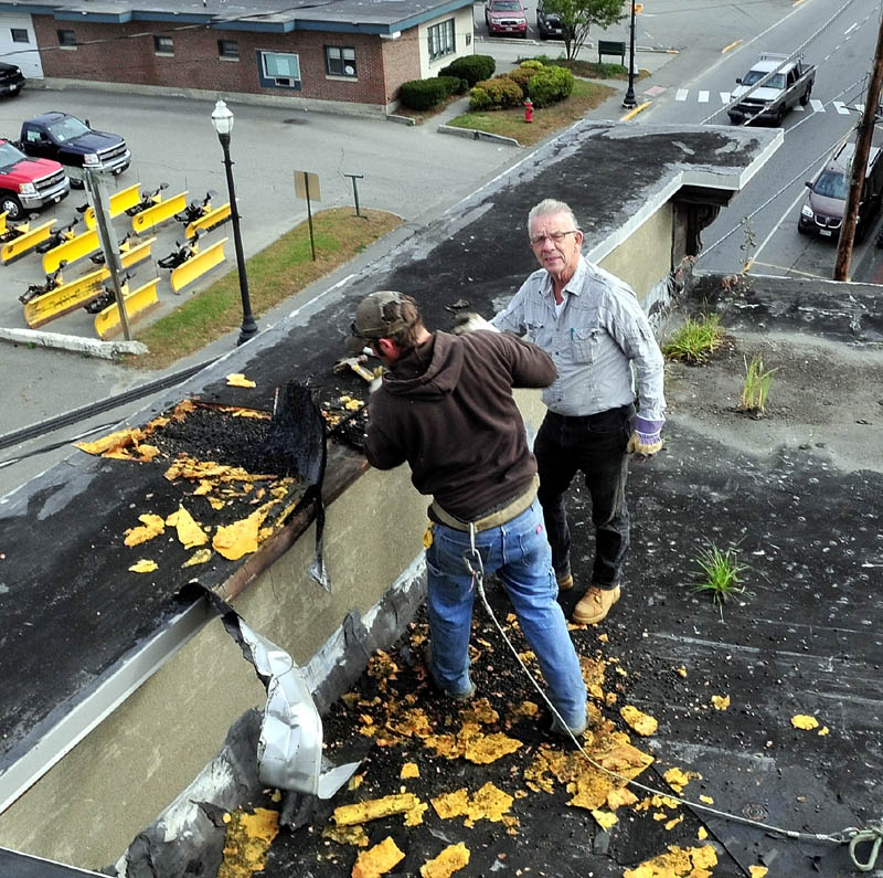 READY TO DROP: Tom McCarthy, right, owner of McCarthy Enterprises, oversees employee Lance Dionne on top of the Sweet Memories of Maine building in Skowhegan that will be torn down along with two other buildings.