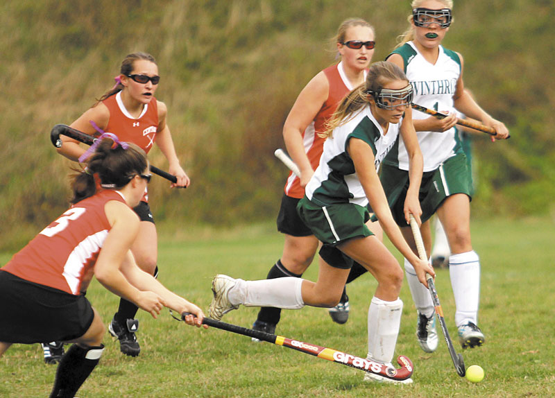 HEADING IN THE RIGHT DIRECTION: Winthrop High School's Emmah Spahr, second from right, pushes the ball past Central High School's Tabby Goldsmith, left, during the first half of a Class C semifinal field hockey game Saturday in Winthrop. Winthrop won 3-0.