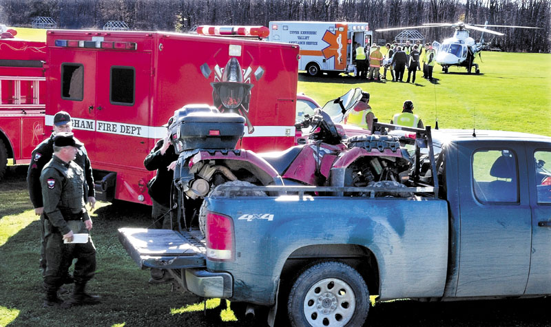 INJURY: Game Warden Rick Clowry, front, and other wardens look at an all-terrain vehicle that lost a rear wheel, sending operator Glen Dow of Madison into a ditch while he was riding in Caratunk on Sunday. Dow is being loaded into a LifeFlight of Maine helicopter at an airport in Bingham.
