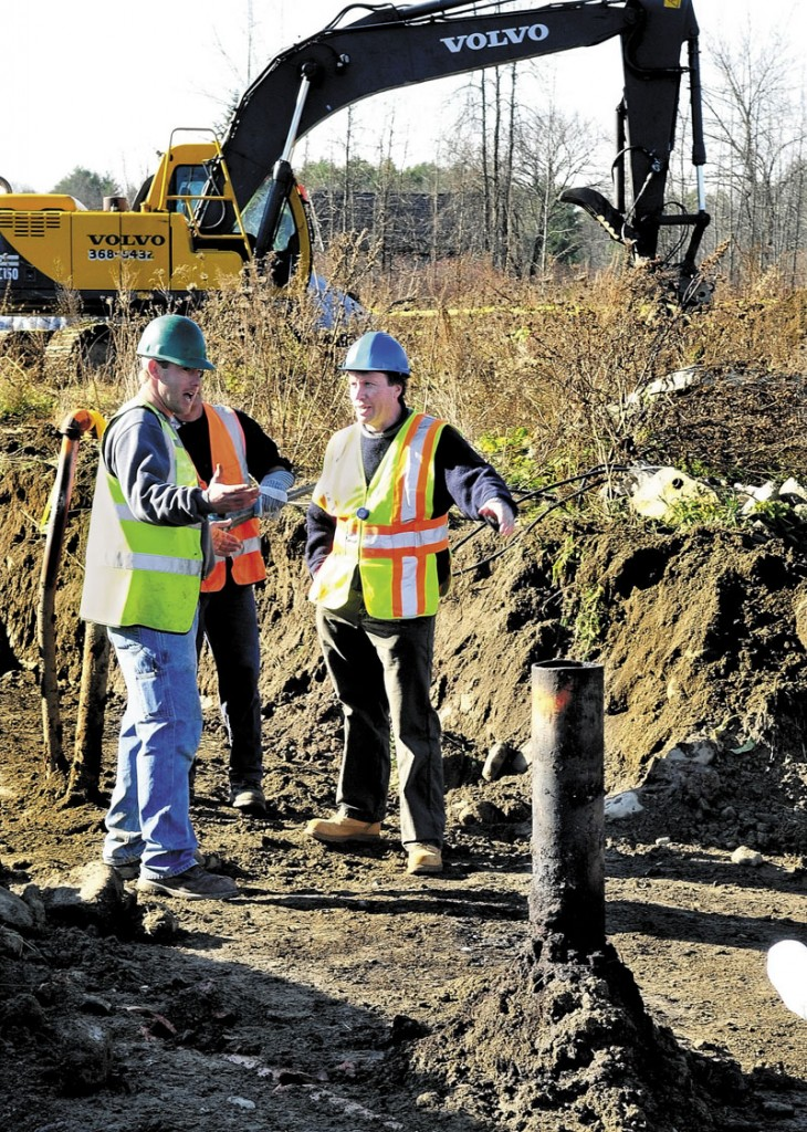CLEANUP: Butch Bowie, right, an environmental specialist with the Maine Department of Environmental Protection, speaks with cleanup crews beside one of six underground waste oil tanks at the former J&A Floral shop in Benton on Wednesday.