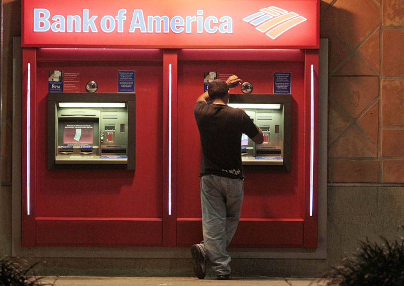 SO MUCH FOR THAT: A Bank of America customer is shown recently at an ATM in Hialeah, Fla. The bank is scrapping its plans to charge a $5 monthly debit card fee after an uproar of customer outrage in recent weeks.