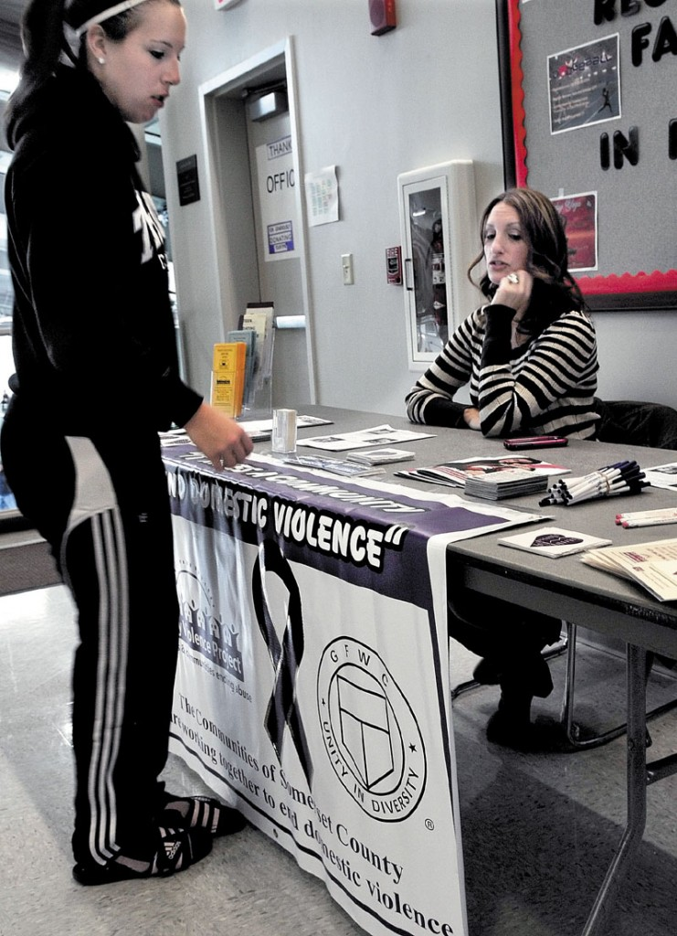IMPORTANT ISSUE: Heidi Olson, right, a volunteer with the Family Violence Project, answers questions from Elizabeth Goodall during the Taylor Tip Off basketball tournament at Thomas College in Waterville on Sunday. The event helps raise awareness of domestic violence.