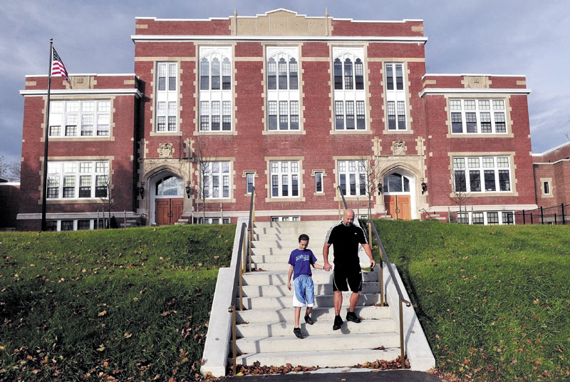 REVIVED: Anika and David Elias walk down the front steps of the renovated Gilman Place in Waterville on Tuesday.
