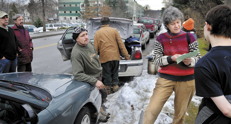 A PERMIT TO ASSEMBLE: Occupy Augusta movement member Diane Messer, second from right, inspects a permit Monday she was directed to fill out by Capitol Police for an application to protest in Capitol Park in Augusta. The group requested a restraining order in U.S. District Court to impede the State of Maine from enforcing the permit, according to Messer.