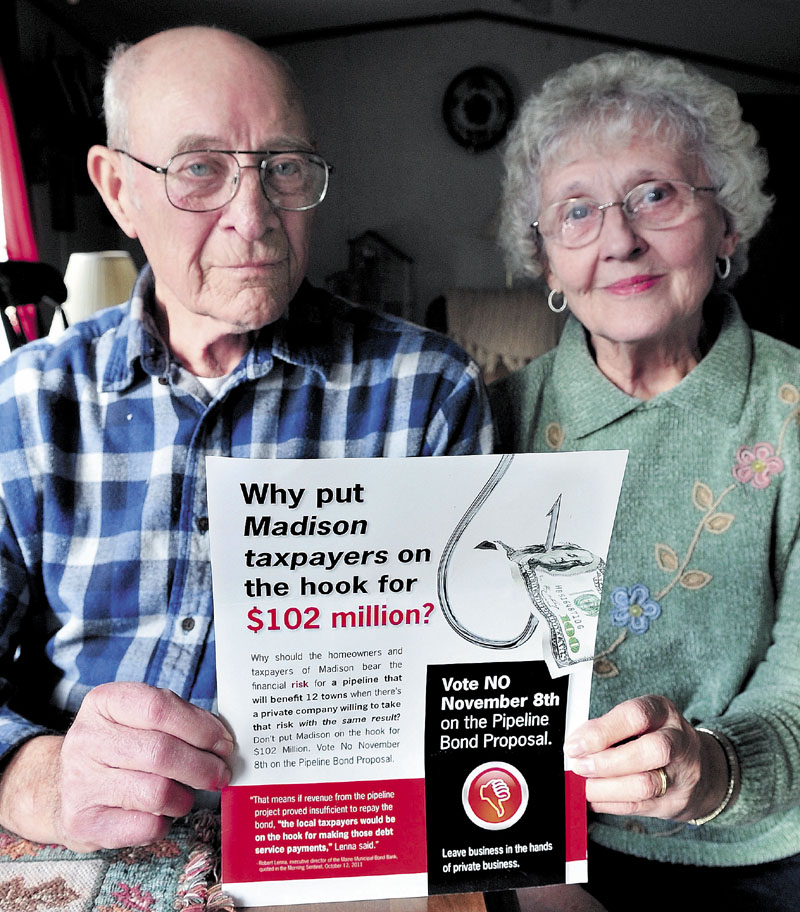 WHY NOT: Walter and Betty Thebarge of Madison hold a flier they received recently urging residents to vote against a town pipeline bond proposal. The couple said they will vote in favor of the proposal.