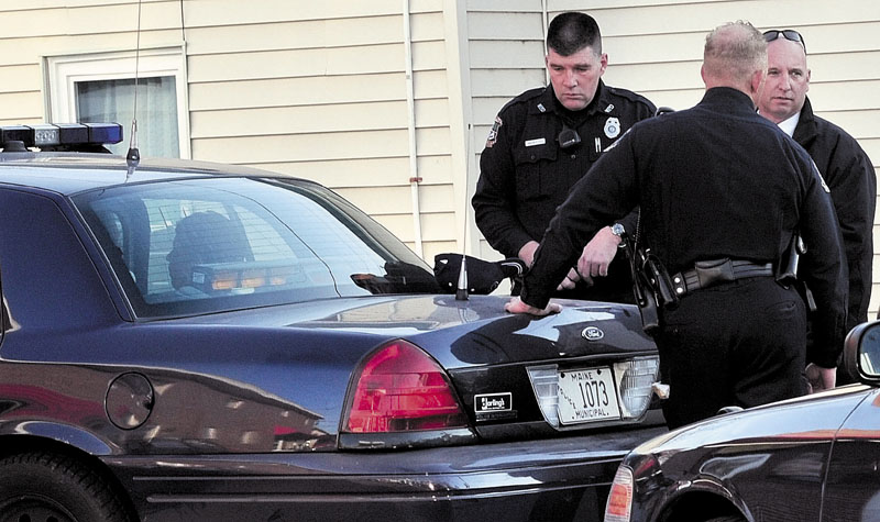 SUSPECT: A male suspect sits in a cruiser at the Big Apple on Elm Street as Waterville police officers Galen Estes, left, Tim Hinton and Detective Sgt. Michael Beneche investigate a robbery at the Bank of America on Monday.