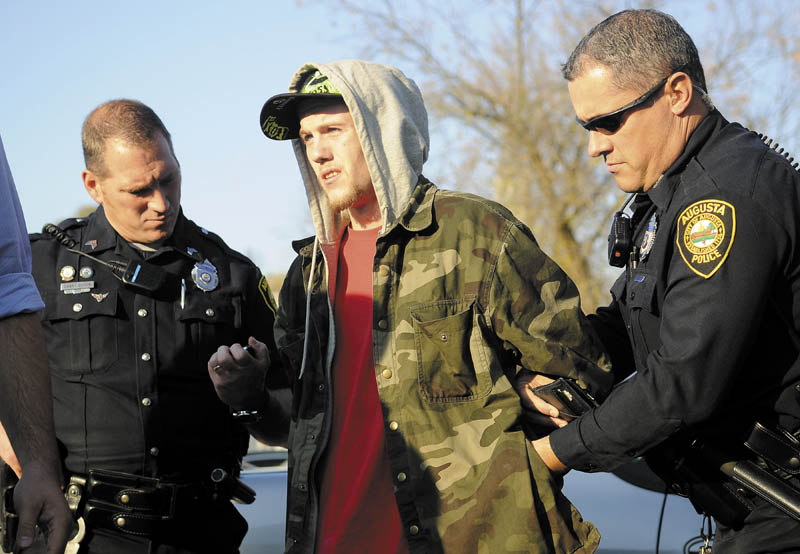 IN CUSTODY: Augusta Police Dept. Sgt. Daniel Boivin, left, and Officer Chris Guay arrest Jake Pilsbury on Monday in Augusta. Pilsbury, 20, a transient who had been staying in the Augusta area, appeared via video Friday in Augusta District Court on charges of burglary and theft. Judge Patrick Ende set bail at $50,000 cash or $100,000 worth of property.