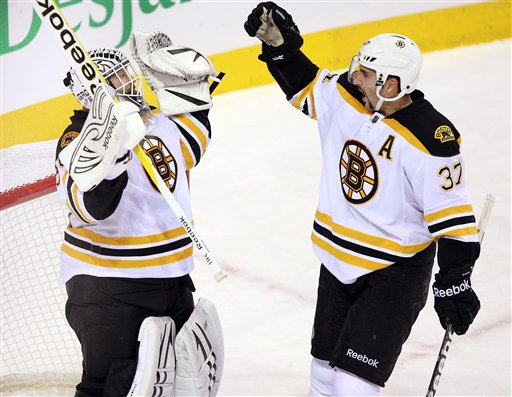 Boston Bruins goalie Tim Thomas (30) celebrates with teammate Patrice Bergeron after defeating the Montreal Canadiens 1-0 Monday in Montreal. Canada Quebec Montreal hockey NHL athlete athletes athletic athletics Canada Canadian competative compete competing competition competitions game games League National play player playing pro professional sport sporting sports team Montreal Canadiens Bell Center Centre Bell Toronto Maple L