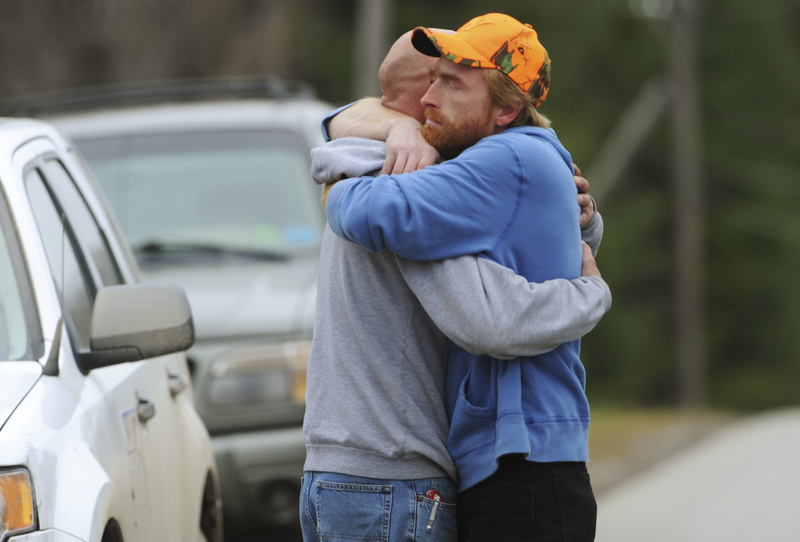 TWO FATALITIES: Jim Curtis, left, brother to Michael Curtis, is comforted by a friend in front of the Piscataquis Valley fairground in Dover-Foxcroft on Tuesday. Michael Curtis was shot and killed by a state trooper after walking into a nursing home and fatally shooting a maintenance worker.