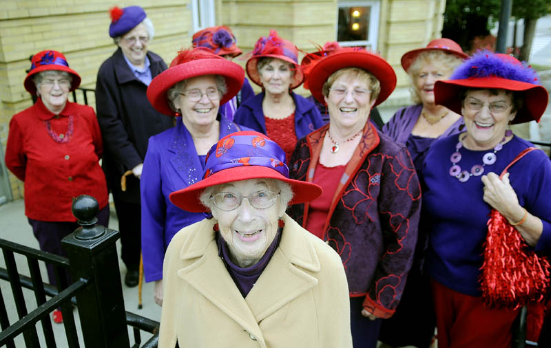 Charlotte Eastman, center, is surrounded Sunday by members of the Augusta Red Hat Society before attending a play at Hallowell City Hall. Eastman, 93, just penned an autobiography and attended the play to celebrate her birthday.