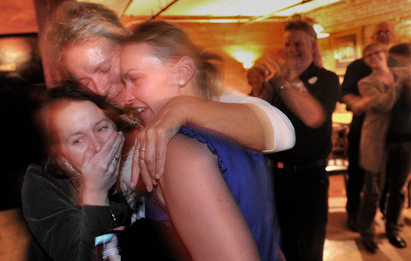 NEW MAYOR: Mayor-elect Karen Heck, center left, hugs her campaign manager, Dana Hernandez, left, and Megan Williams after poll results showed Heck had won the mayoral election during a celebration Tuesday night at 18 Below Raw Bar in Waterville.