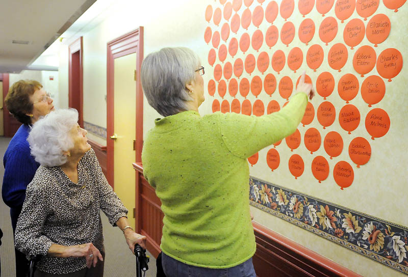 A DECADE LATER: Brenda Gross, right, helps her mother, Pauline Crocker, center, identify residents of the Inn at City Hall with Augusta elderly apartment complex administrator Lynda Pratt on Thursday, when they celebrated the 10th anniversary of the residence.