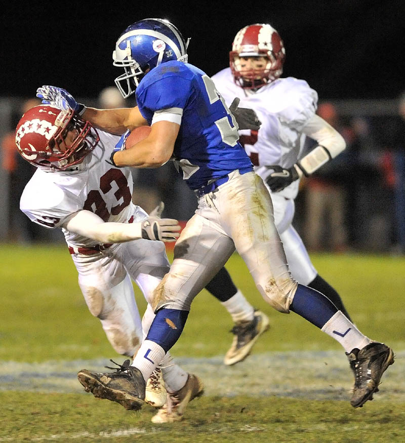 LOOK OUT: Lawrence High School running back Shaun Carroll, right, stiff arms Bangor High School defender Nick Sherwood in the second quarter of the Bulldogs' 40-14 win in the Pine Tree Conference Class A title game Friday in Fairfield.