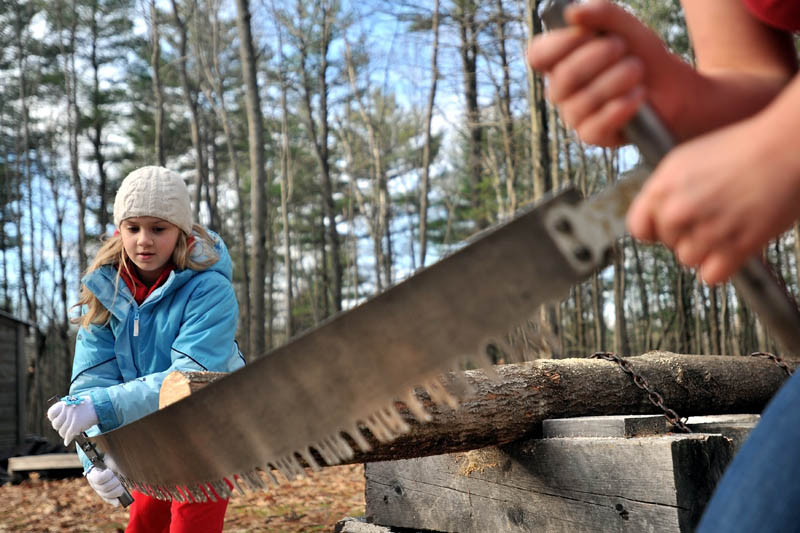 LEARNING NEW SKILLS: Emma Parrish, 9, of Oakland, handles a cross-cut saw with the help of Colby College sophomore Liz Schell as part of the Adventure Girls Series sponsored by Hardy Girls Healthy Women on Saturday afternoon in Waterville.