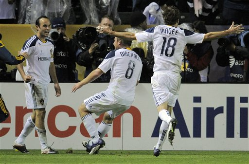 Los Angeles Galaxy forward Landon Donovan, left, celebrates his goal with teammates midfielder Chris Birchall, center, and forward Mike Magee during the second half of their MLS Cup championship soccer match against the Houston Dynamo, Sunday in Carson, Calif. The Galaxy won 1-0.