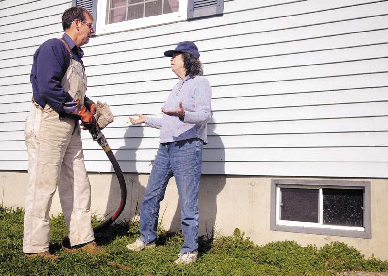 FILL IT UP: Danny Chapman speaks with Elizabeth Street as he fills an oil tank in Chelsea belonging to her daughter with heating oil. The U.S. average for home heating oil on Nov. 21 was $3.93 per gallon; in Maine it was $3.75, according to U.S. energy numbers.