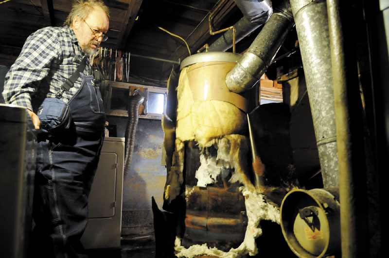 """Craig Johnson surveys the hot water heater that was condemned last month in the basement of his Augusta home. Johnson — who has cancer — and his wife, Donna, went without heat and hot water for about a month before finding a solution this past week: They purchased a new hot water heater with their own money and a second heating technician fixed the oil tank leak, enabling the furnace to operate safely. """"We had two angels come and help us,"""" Donna said, referring to the technicians. """"We're all set now."""""""