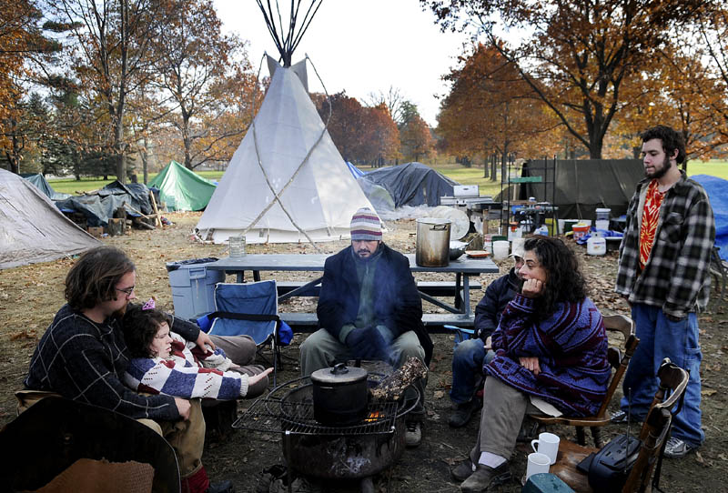 Members of the Occupy Augusta movement warm up Sunday morning in Capitol Park in Augusta. They said they plan on residing in the park for the winter.