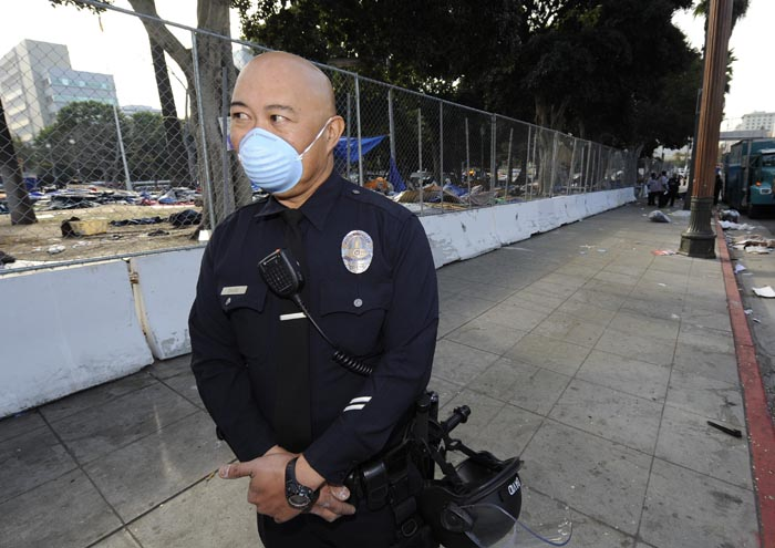 A Los Angeles police officer stands guard as city crews clean up and erect a fence around City Hall after the LAPD broke up the large encampment of protesters who had been camping there for the past two months.
