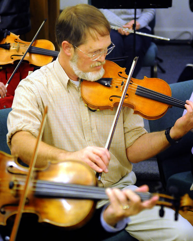 Nate Saunders rehearses Wednesday, with the violin he made. during a session with the Augusta Symphony Orchestra in Manchester.