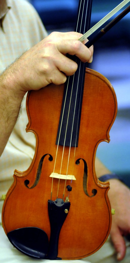 Nate Saunders holds his homemade violin, named after his wife, Cordelia, during a rehearsal Wednesday with the Augusta Symphony Orchestra in Manchester.