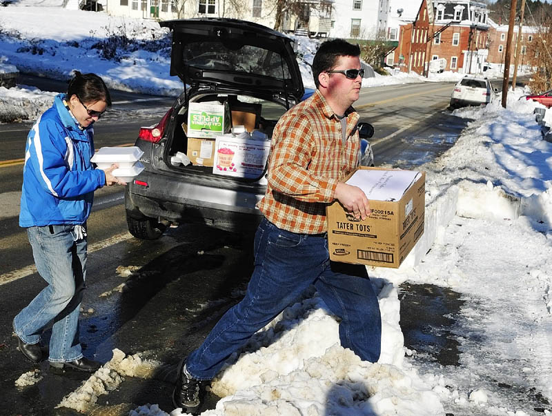 Erica Atkinson, left, and her husband Joshua Atkinson, carry boxes of Thanksgiving dinners from their car to a Richmond home Thursday morning. They delivered 66 meals to the Richmond area. In addition to meals served to people in the cafeteria, there were 335 meals delivered from the dinner sponsored by the Augusta Valley Scottish Rite Masons.
