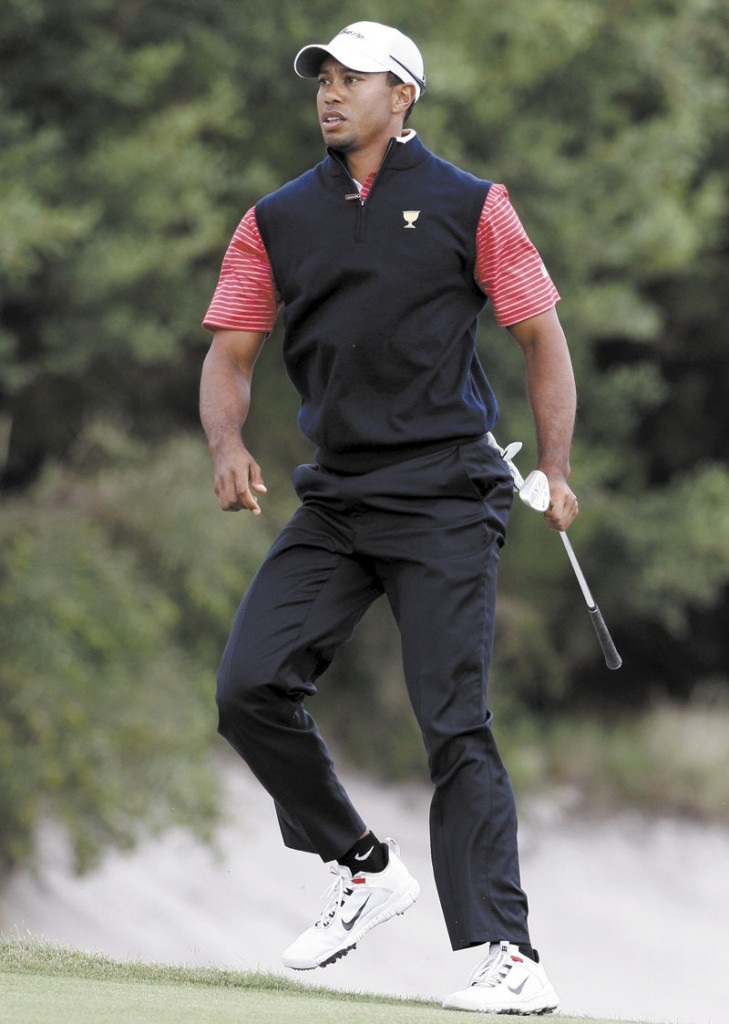 Tiger Woods jumps out of a bunker onto the 15th green during the Presidents Cup Sunday at Royal Melbourne Golf Course in Melbourne, Australia.