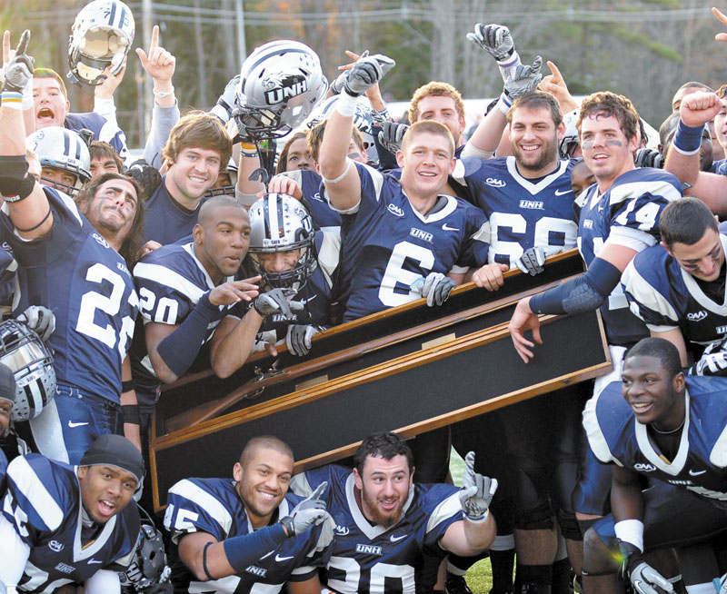 New Hampshire players hold up the Bryce-Cowell Musket after they defeated Maine 30-27 Saturday at Cowell Stadium in Durham, N.H.,
