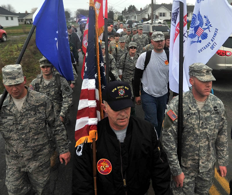 Staff photo by Michael G. Seamans Ronald Raymond, front center, leads a group of veterans to the Winslow Memorial Park as part of Veteran's Day memorial on Friday. The group marched 21 miles from the Vietnam Memorial in Augusta to Winslow.